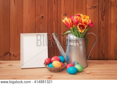 Easter Concept. Colorful Tulips In Watering Can, Easter Eggs In Wicker Basket And White Frame On Woo