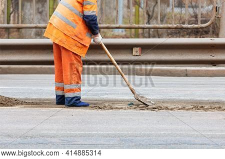 A Road Service Worker Uses A Shovel To Scrape Off Accumulated Sand And Debris Between The Lanes Of T