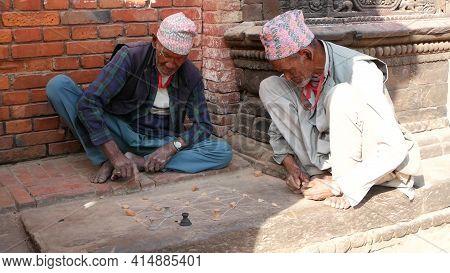 Bhaktapur, Kathmandu, Nepal - 18 October 2018 Senior Men Playing Intellectual Game On Sidewalk. Aged
