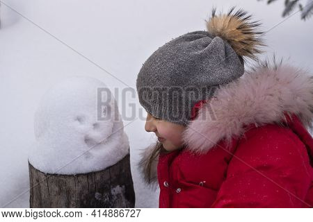 A Girl In A Winter Hat And A Red Jacket With A Small Snowman In The Snow. The Concept Of Winter Fun