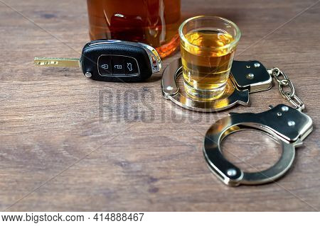 Close-up Of Car Key On Background Of Shot Glass Of Whiskey With Metal Police Handcuffs And Bottle Of