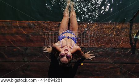 Woman Sit On A Pier In Sunglasses And Swimming Suit. Girl Rest On A Flood Wood Underwater Pier. Lady