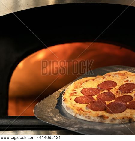 Hot Pizza Freshly Baked. Ready To Eat Pepperoni Pizza With Salami Against Of Open Burning Fire In Ov