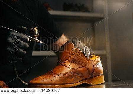 Close-up Side View Of Unrecognizable Shoemaker Wearing Black Gloves Spraying Paint Of Light Brown Le