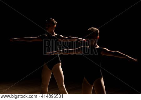 Young Ballerinas Rehearsing In The Ballet Class. They Perform Different Choreographic Exercises And