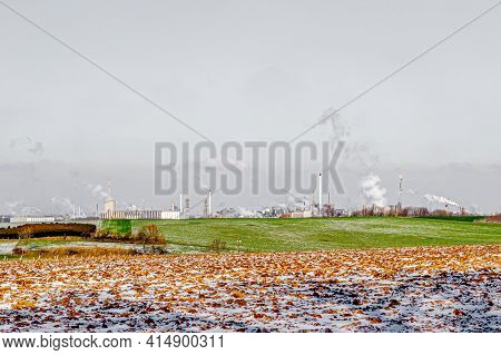 Uncultivated Dutch Farmland With Remnants Of Snow, Green Grass And An Industrial Complex In The Back
