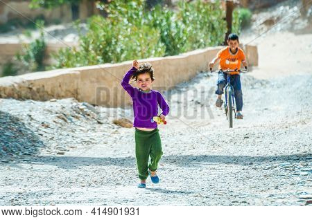 Aouli, Morocco - April 10, 2015. Cute Moroccan Berber Girl Running And Waving Toward To The Tourists
