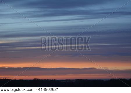 Colorful Sunset In Winter. Striped Clouds In The Sky
