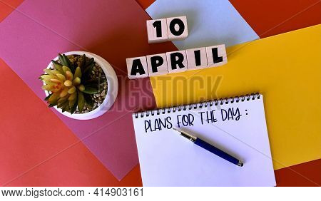 April 10  On Wooden Cubes. Next To It Is A White Notebook With Plans For The Day Written On It , A P