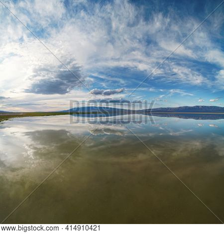 The evening cloudy sky is reflected in the Uureg Nuur Lake