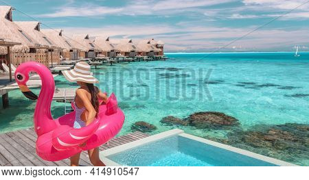 Travel vacation fun tourist woman enjoying luxury summer holidays at Bora Bora overwater bungalow swimming with flamingo pool toy float at infinity pool by turquoise ocean. Tahiti getaway destination.