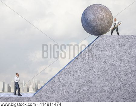 businessman pushes big concrete sphere towards the slope where there is another man. concept of unfair competition.
