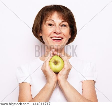 Portrait of a beautiful elderly woman holding an apple, smiling, isolated on white background. Happy Woman Holding Granny Smith Apple.