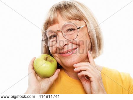 Food, health and old people concept: Portrait of senior woman holding an apple over white background
