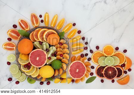 Immune boosting citrus fruit high in fibre with cranberries, oranges, lemons, limes and grapefruit also high in antioxidants, anthocyanin and vitamin c. Natural health care concept. On marble.