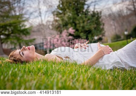 A beautiful expectant mother poses in an outdoor environment