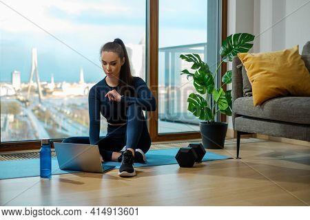 Brunette in sportswear surfs internet seeking videos on laptop sitting on blue mat near window and green plant on glazed balcony