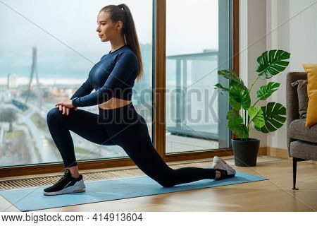 Woman in tracksuit practices exercise in yoga warrior pose on mat near panoramic window on balcony with view on city in spring