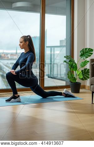 Slender brunette woman in tracksuit practices yoga in warrior position on floor mat near panoramic window on glazed balcony