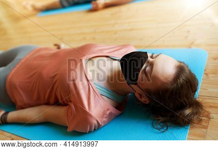fitness, sport and health care concept - woman wearing black face protective mask for protection from virus disease doing yoga corpse pose on mats at studio