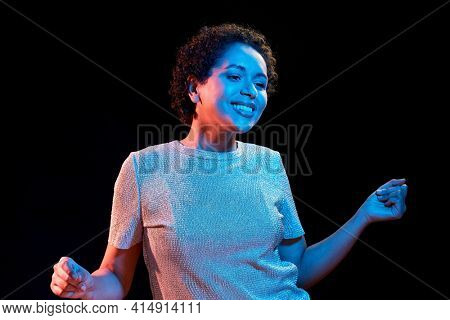 leisure, clubbing and nightlife concept - smiling young african american woman dancing over ultraviolet neon lights on black background