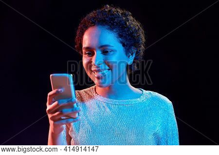 nightlife, technology and people concept - happy young african american woman with smartphone in neon lights over black background