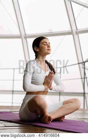 Brunette peaceful woman meditating during yoga practice indoors