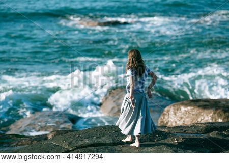 Woman dancer is engaged in choreography on the Atlantic ocean coast.