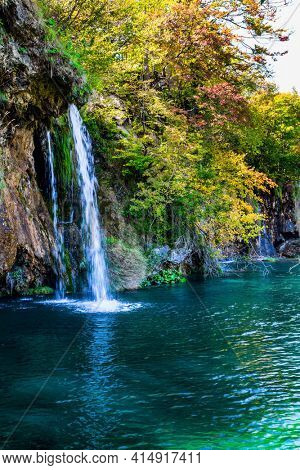 Many picturesque waterfalls flow along the clay cliffs. The transparent shallow lake reflects the forest. Travel to Central Europe. Plitvice Lakes Park in Croatia