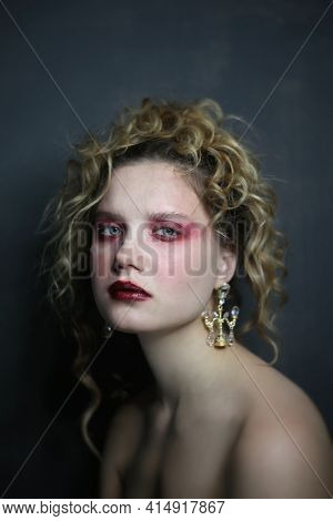 Vintage style portrait of young beautiful woman with red eyeshadow makeup and fancy chandelier earrings, selective focus