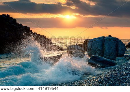 Sea Ocean Wave hit the rock at beach, sea water splash up to the sky with sun. Sunset Sundown at Sea. Storm. Seascape. Focus on foreground