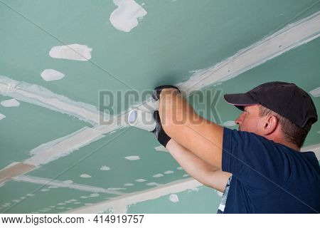 Worker glues mesh to drywall seams