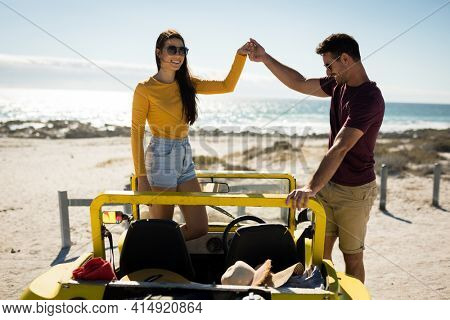 Happy caucasian couple in beach buggy by the sea holding hands. beach break on summer holiday road trip.