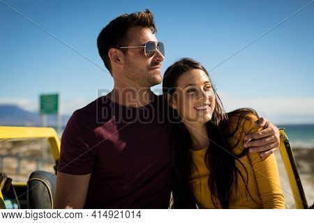 Happy caucasian couple sitting on beach buggy by the sea embracing. beach break on summer holiday road trip.