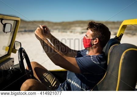 Caucasian man wearing face mask sitting in beach buggy taking picture. beach stop off on summer holiday road trip during coronavirus covid 19 pandemic.