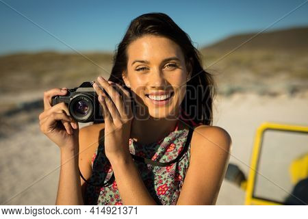 Happy caucasian woman next to beach buggy by the sea taking picture. beach break on summer holiday road trip.