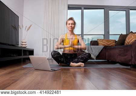 Woman doing online yoga at home. Female trener teaches asana in video conference. Health care, authenticity, sense of balance and calmness.