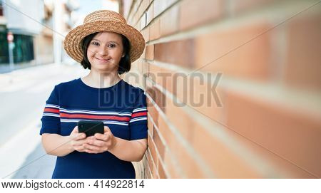 Beautiful brunette woman with down syndrome at the town on a sunny day using smartphone leaning on a bricks wall