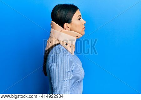 Beautiful brunette woman wearing cervical collar looking to side, relax profile pose with natural face with confident smile.