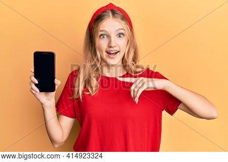 Beautiful young caucasian girl holding smartphone showing screen celebrating crazy and amazed for success with open eyes screaming excited.
