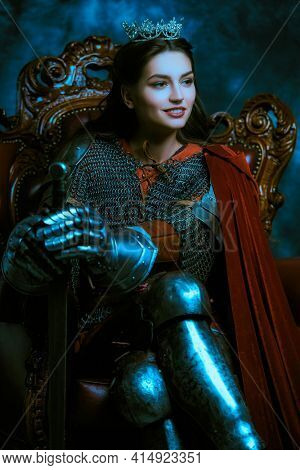Portrait of a beautiful medieval queen in knightly armor sitting on a throne and smiling. History of the Middle Ages.