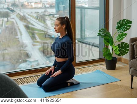 Slender young woman with brown hair in turquoise tracksuit sits in yoga pose on mat near panoramic window with street view