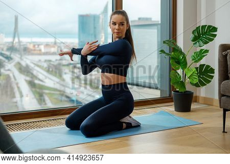Brunette woman with ponytail in green tracksuit does exercise on mat near panoramic balcony window with city street outside