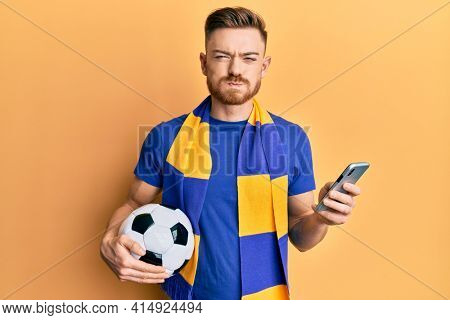 Young redhead man wearing hooligan scarf and using smartphone puffing cheeks with funny face. mouth inflated with air, catching air.