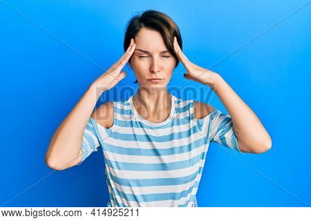 Young brunette woman with short hair wearing casual striped t-shirt suffering from headache desperate and stressed because pain and migraine. hands on head.