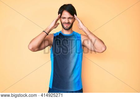 Handsome hispanic man wearing sportswear suffering from headache desperate and stressed because pain and migraine. hands on head.
