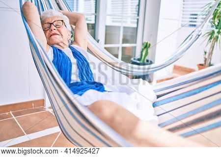 Elder senior woman with grey hair smiling happy relaxing on a hammock at home