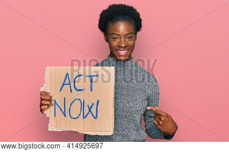 Young african american girl holding act now banner smiling happy pointing with hand and finger