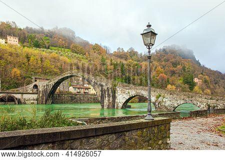 Ponte della Maddalena (Devil's Bridge) over the Cercchio River. Medieval bridge with magnificent architecture. Italy. Province of Tuscany. Outskirts of Bagni di Lucca
