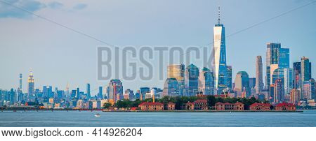 New York, New York, USA skyline from the harbor with Ellis Island at dusk.